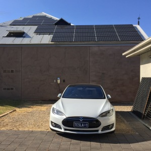 Model S in front of solar panels - make your own transport energy